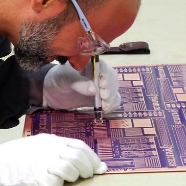 Atotech-Mitarbeiter begutachtet Leiterplatte nach Kupferabscheidung mit einem Handmikroskop