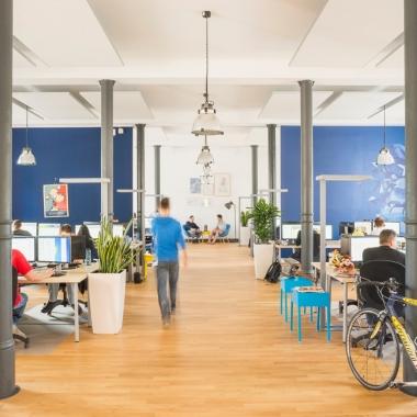 Dich erwarten große, offene Büroräume in denen teamweise gearbeitet wird.