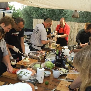 Während Simon und Gunar beim Weber Grillkurs auf Mallorca Zwiebeln für die Vorspeise schneiden, sind Kai, Christoph und Tobi dabei das Spanferkel für den Grill vorzubereiten