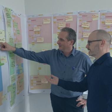 Thomas und Robert diskutieren kontrovers am Kanban Board