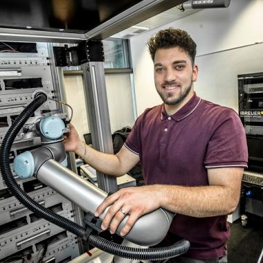 Ein Kollege aus der Verfahrensentwicklung mit einem von ihm programmierten Roboterarm für OBU-Tests.