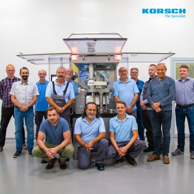 """KORSCH-Mitarbeiter vor der neuesten Maschine - die """"X 3""""."""