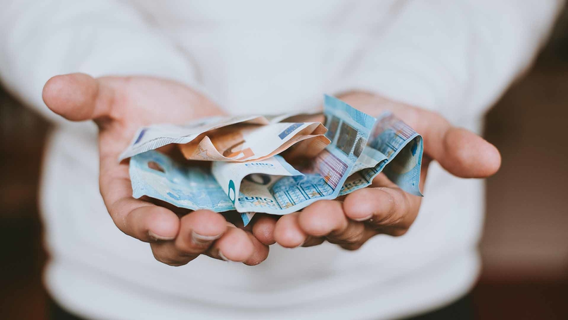 Euro bills placed in both palms of hands