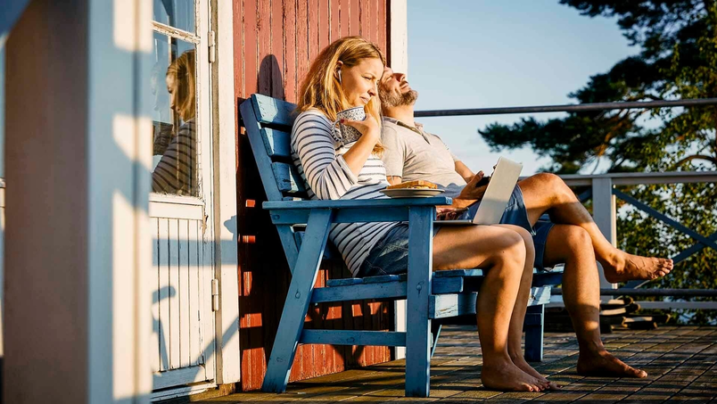 Woman working on a laptop and man enjoying sun, both on a bench on a patio