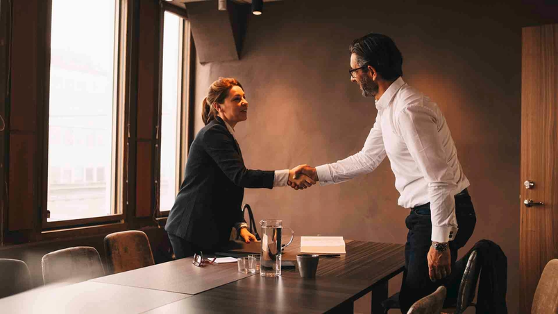 Man and woman shaking hands in an office meeting room